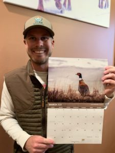 Tanner Cherney of Peak Productions holding the 2020 Pheasants Forever Calendar with his photo used for March.